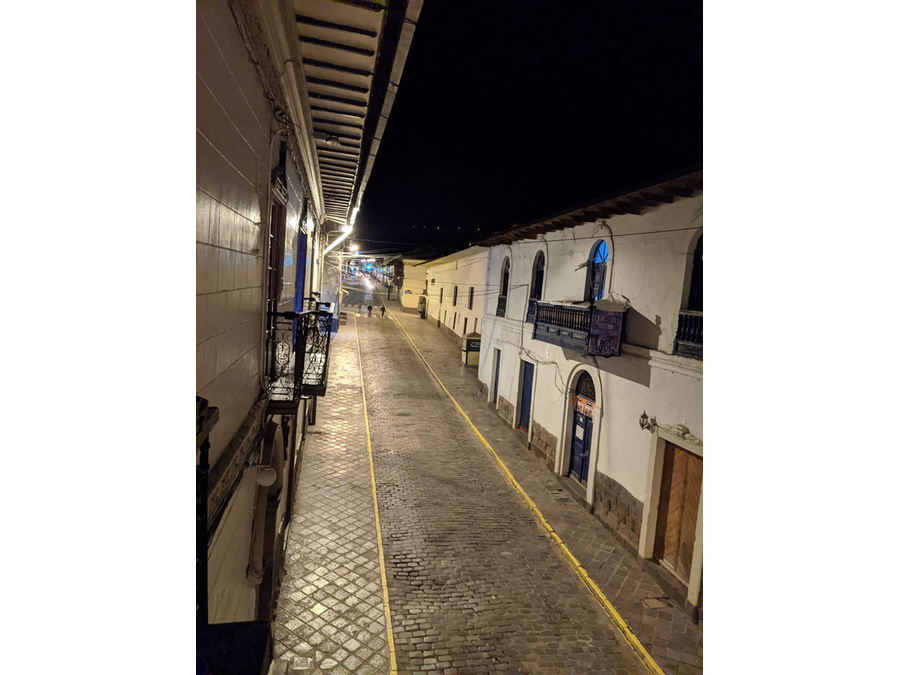 A nighttime view of a street in Cusco, Peru, with just two solitary pedestrians out before the 8 p.m. curfew.