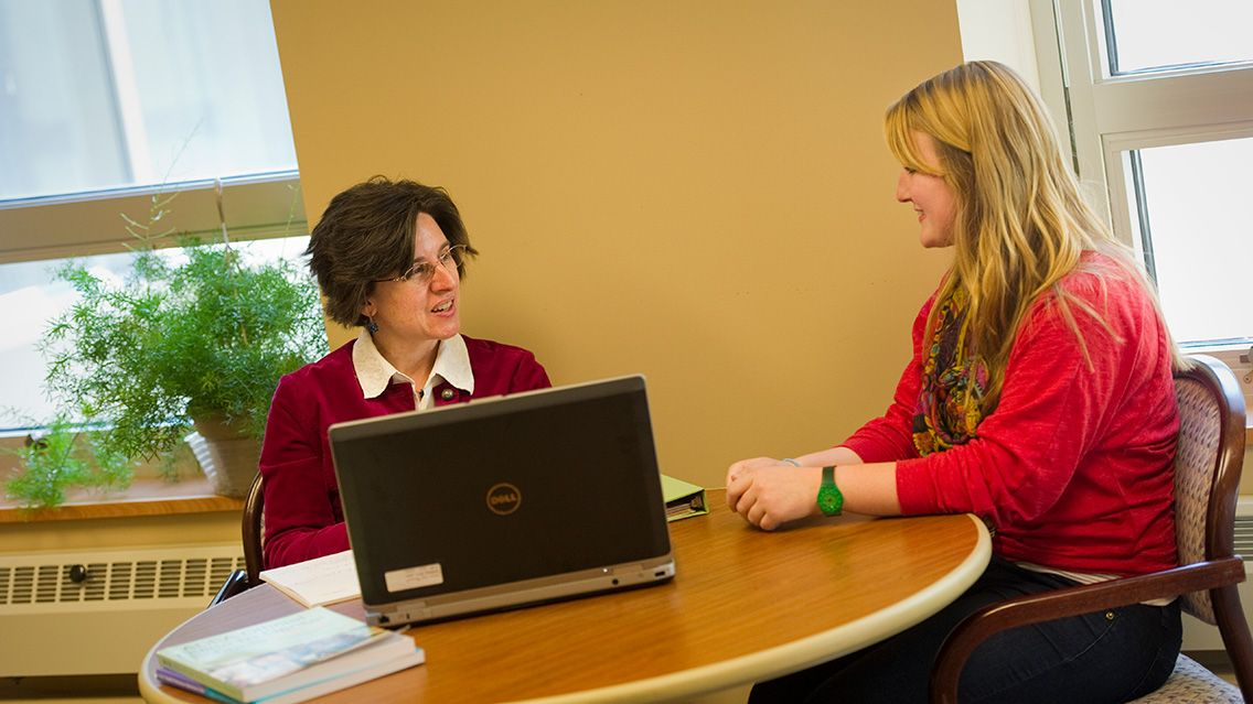From 2013: Bennett, left, counsels psychology major Dana Sautter '15. Photo by Duane Zehr.
